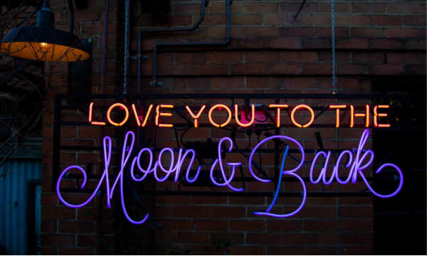 "Neon sign that reads ""love you to the moon and back."""