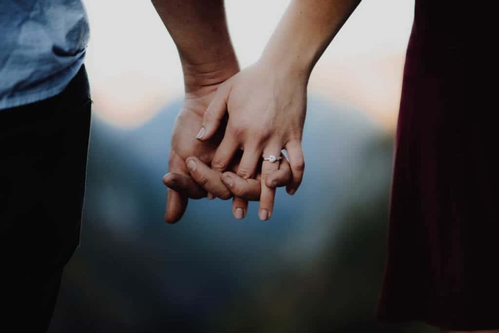 married couple's hands intertwined together. Ring on woman's finger.