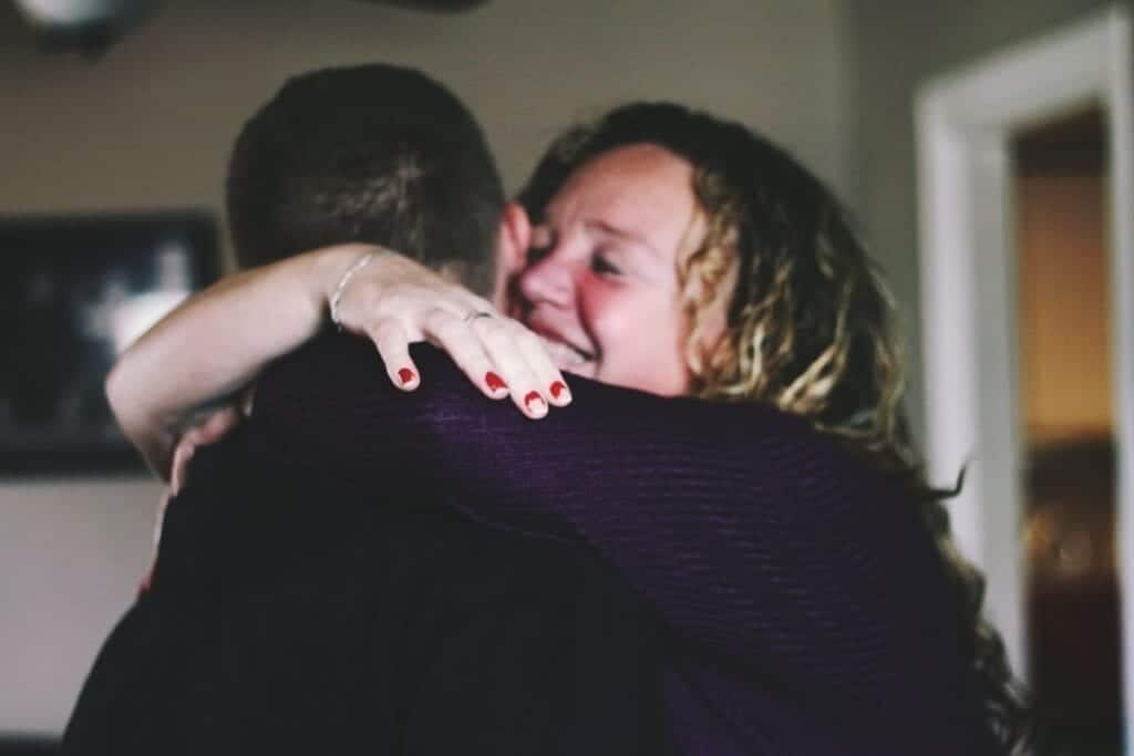 Mom hugging adult son and smiling.