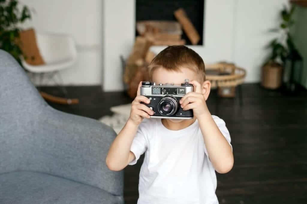 Boy taking holding a camera over his face and taking a picture.