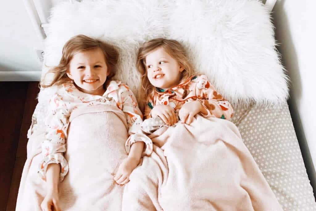 Two little girls laying in bed on a fluffy pillow and smiling.