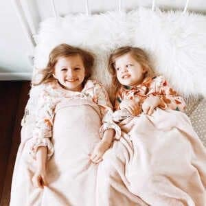 Two young sisters laying in bed and smiling