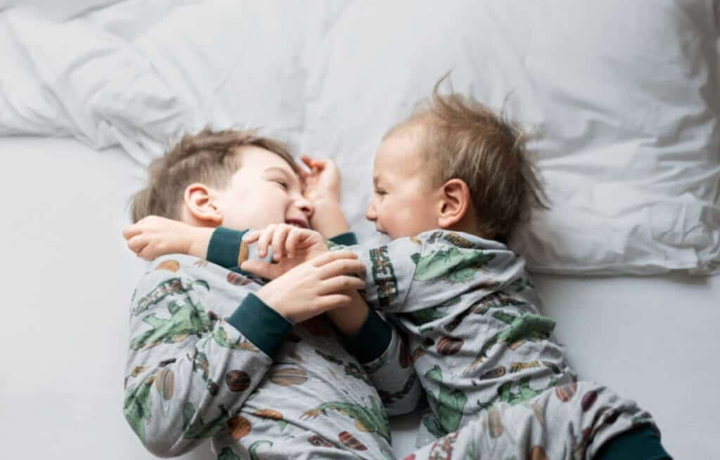 Two boys - a toddler and older infant - hugging and play wrestling on the bed.