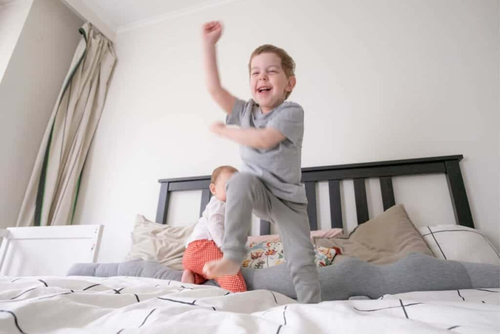 Toddler boy jumping on bed. Little baby sister behind him in bed.