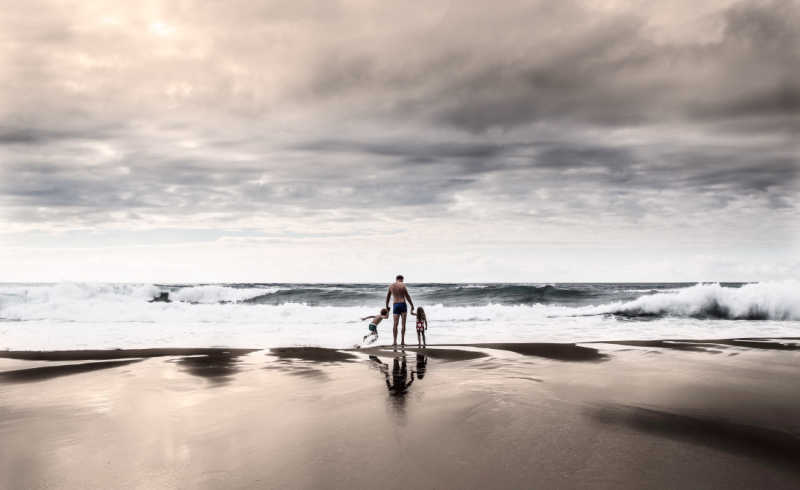 Dad with two kids at the ocean holding hands on the beach.