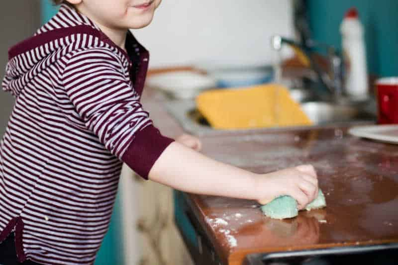 child wiping counters with a sponge.