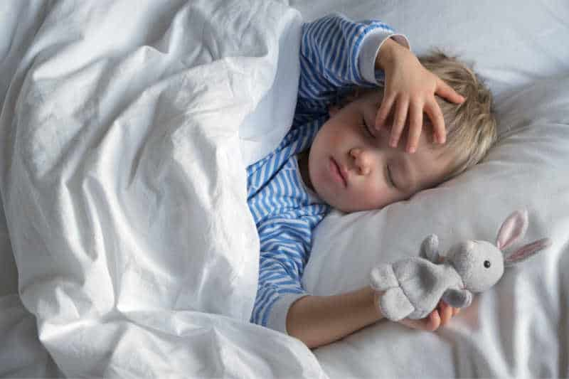 1 year old sleeping during naptime in bed and holding small stuffed bunny
