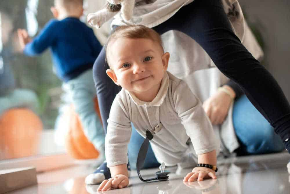 baby smiling and crawling on the ground